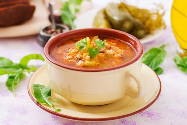 Sopa com pepinos em conserva e cevadinha - rassolnik em uma mesa de luz.