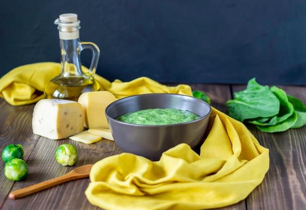 Sopa creme com espinafre e queijo superfície de madeira