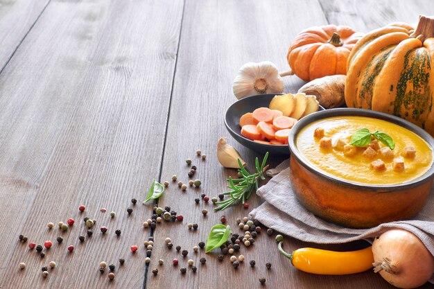 Sopa creme de abóbora com cenoura e gengibre em uma tigela de cerâmica na madeira