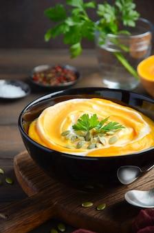 Sopa creme de abóbora com creme e sementes de abóbora na mesa de madeira.