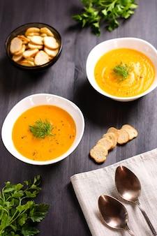 Sopa creme de abóbora com croutons e endro fresco e salsa na mesa de madeira