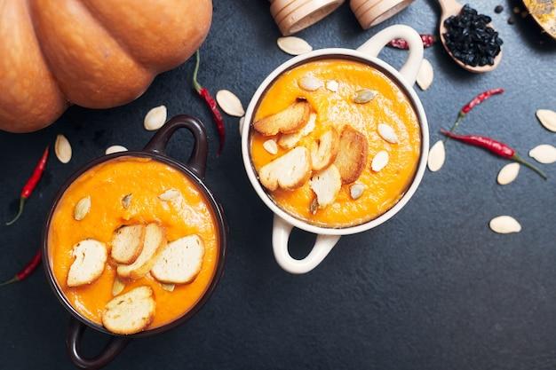 Sopa creme de abóbora com croutons em uma mesa preta com especiarias. foto de alta qualidade