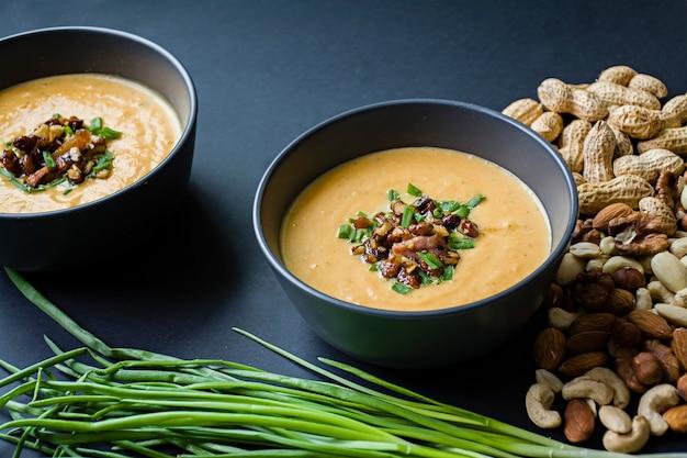 Sopa creme de abóbora com ervas e nozes, servido em uma tigela escura.