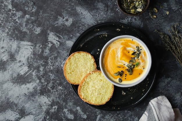 Sopa creme de abóbora com lentilhas e sementes de abóbora em um fundo escuro