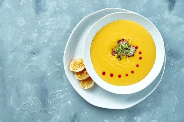 Sopa creme de abóbora com polvo e croutons em uma tigela branca. sopa cremosa de frutos do mar