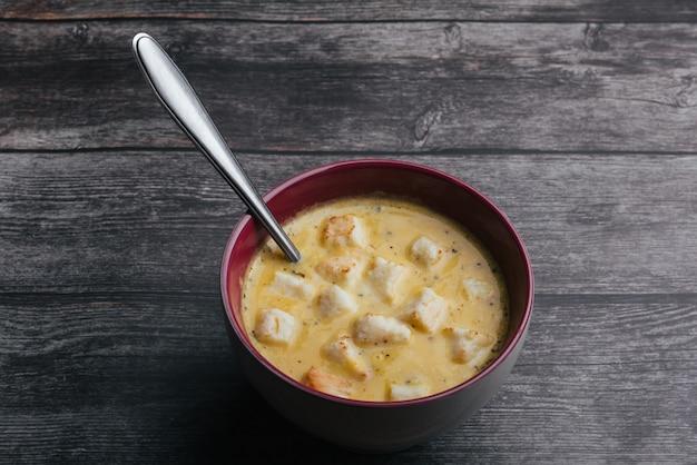 Sopa creme de abóbora com salsa em uma tigela e uma colher