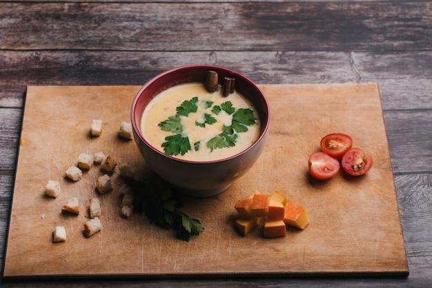 Sopa creme de abóbora em uma tigela com salsa na mesa de madeira com biscoitos e tomates. comida tradicional de outono para o halloween