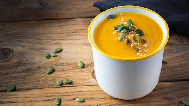 Sopa creme de abóbora vegetariana com sementes em tigela branca