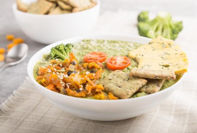 Sopa creme de brócolis verde com biscoitos em uma tigela branca, vista lateral