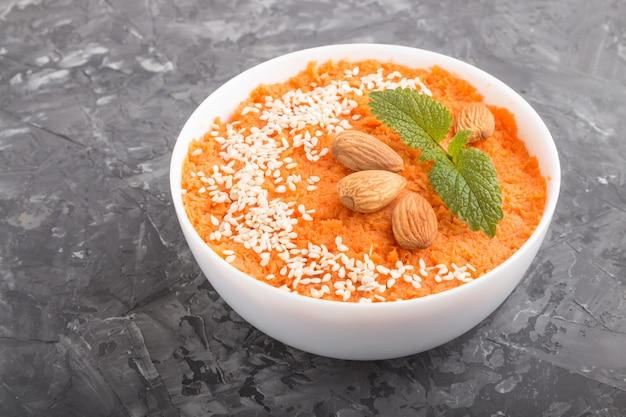 Sopa creme de cenoura com sementes de gergelim e amêndoas em tigela branca em um concreto preto. vista lateral.