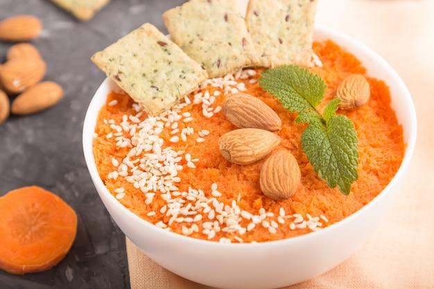 Sopa creme de cenoura com sementes de gergelim e lanches em tigela branca sobre um fundo preto de concreto. vista lateral, close-up.