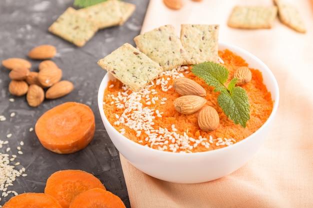 Sopa creme de cenoura com sementes de gergelim e lanches na tigela branca sobre um concreto preto. vista lateral, close-up.