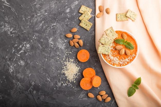 Sopa creme de cenoura com sementes de gergelim e lanches na tigela branca sobre um concreto preto. vista superior, copyspace.