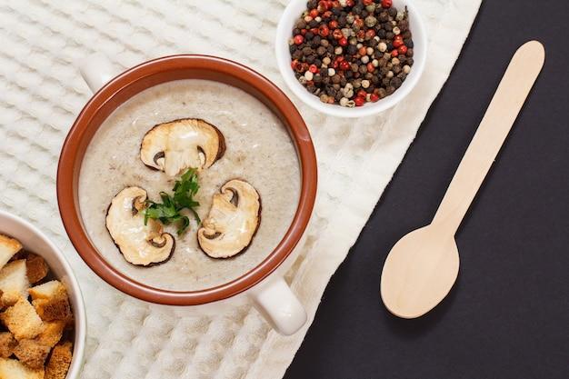 Sopa creme de cogumelos caseiros com cogumelos fatiados em tigela de porcelana, colher de pau, pimenta da jamaica e torradas em um pano de prato. vista do topo.