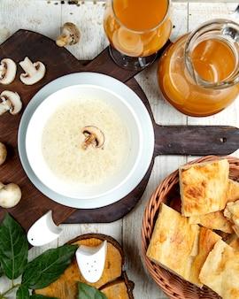 Sopa creme de cogumelos em uma placa de madeira