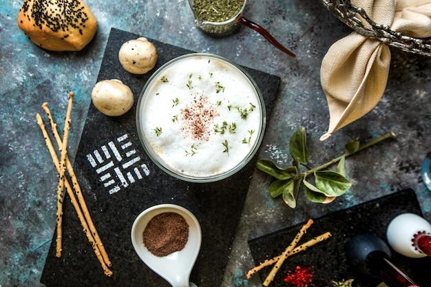 Sopa creme de cogumelos servida com ervas e especiarias.