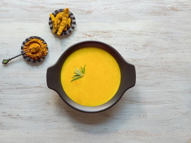 Sopa creme de curcuma saudável na mesa de madeira branca