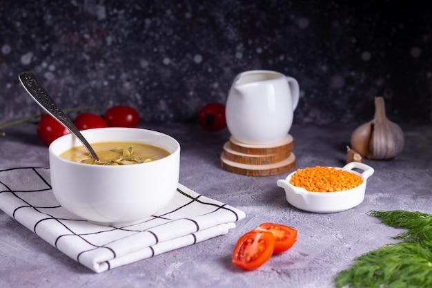 Sopa creme de lentilha e abóbora com endro em um prato branco com creme em suportes de madeira sobre uma superfície cinza