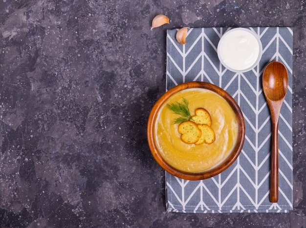 Sopa creme de lentilha e abóbora com endro em uma placa de madeira com uma colher de pau, um prato com creme de leite e alho