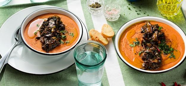 Sopa creme de lentilhas vermelhas com tomate e cogumelos selvagens fritos em cima da mesa. alimento vegan saudável para toda a família
