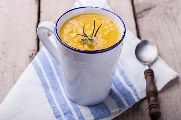 Sopa-creme de milho com pasta de curry e alecrim, em uma caneca.