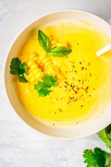 Sopa creme de milho vegan em tigela branca sobre um fundo cinza, vista superior