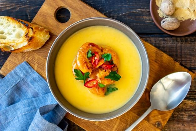 Sopa creme de queijo com camarão grelhado em um fundo de madeira.