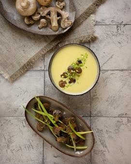 Sopa creme de queijo com cogumelos assados e cebolinha. vista do topo