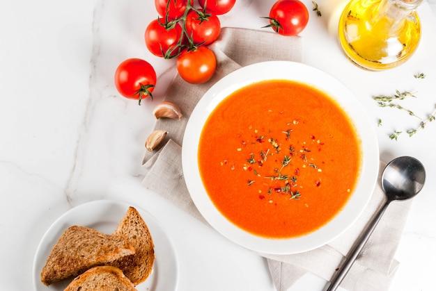Sopa creme de tomate com azeite e ervas, com pão torrado, sobre fundo de mármore branco, copie a vista superior do espaço