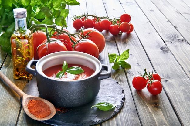Sopa creme de tomate em panela de cerâmica preta, servida com creme e manjericão