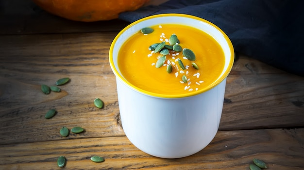 Sopa creme vegetariana com abóbora e sementes em tigela branca