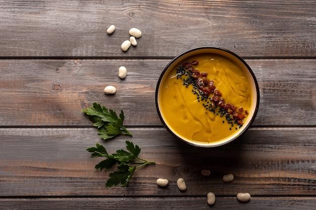 Sopa cremosa caseira com mistura de feijão com pimenta vermelha e gergelim preto sobre fundo de madeira
