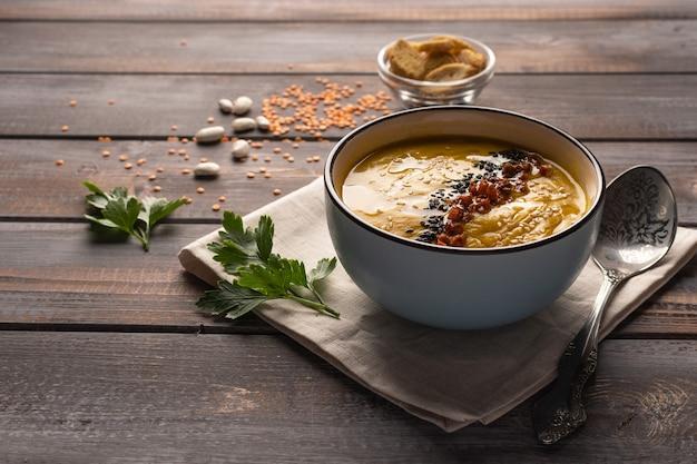 Sopa cremosa caseira com uma mistura de feijão e especiarias num guardanapo sobre um fundo de madeira com