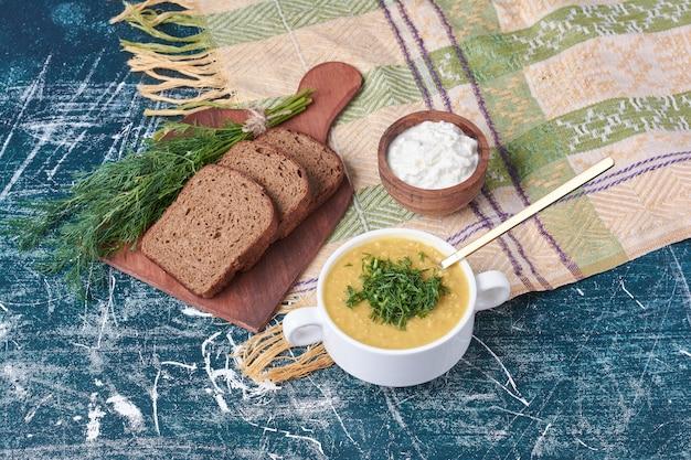 Sopa cremosa com ervas e torradas de pão.