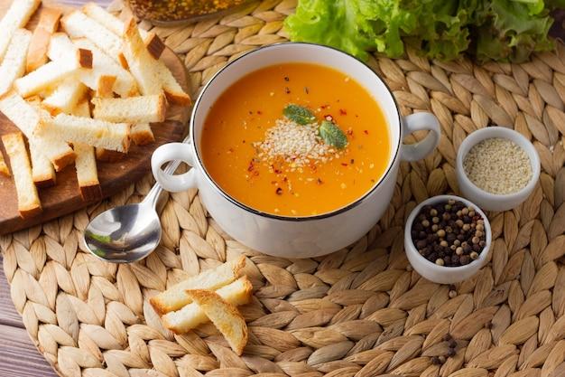 Sopa cremosa de abóbora em copo branco com croutons
