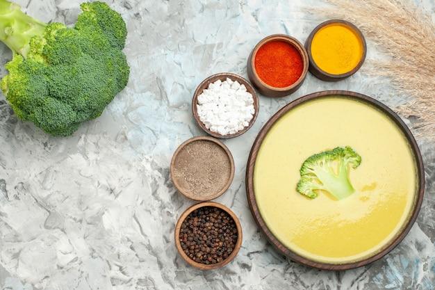 Sopa cremosa de brócolis em uma tigela marrom com especiarias diferentes e brócolis fresco na mesa cinza