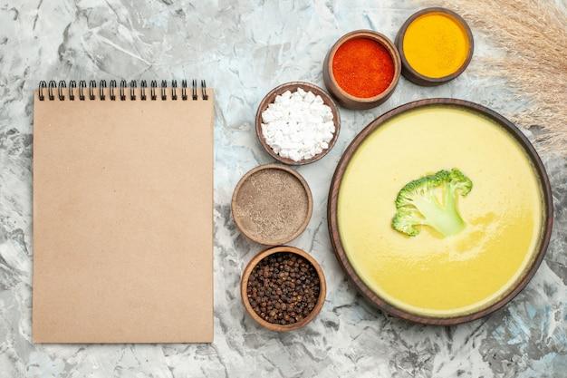 Sopa cremosa de brócolis em uma tigela marrom e temperos diferentes ao lado do caderno na mesa cinza