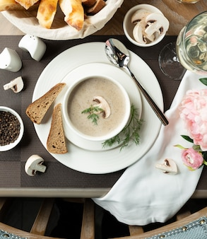 Sopa cremosa de cogumelos com fatias de pão.