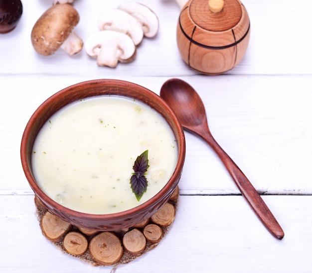 Sopa cremosa de cogumelos em um prato redondo marrom