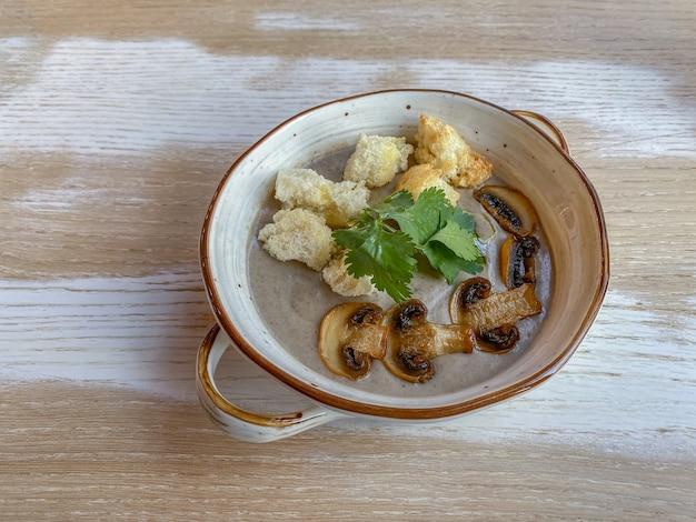 Sopa cremosa de creme com cogumelos e pão torrado na mesa de madeira