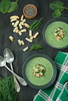 Sopa cremosa de espinafre com bolachas, ervas e sementes de chia. sopa verde, servido em uma tigela sobre uma mesa de madeira. postura plana.