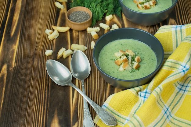 Sopa cremosa de espinafre com bolachas, ervas e sementes de chia. sopa verde, servido em uma tigela sobre uma mesa de madeira.