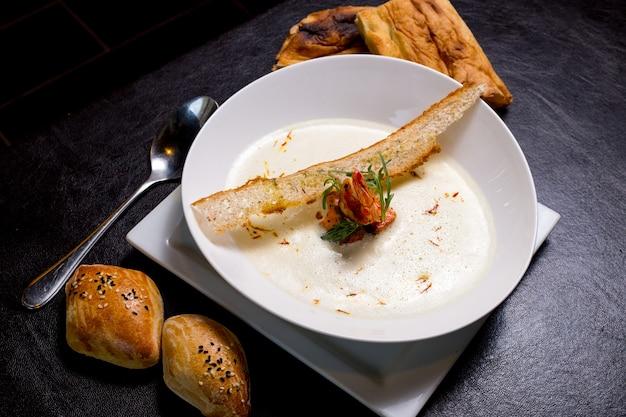 Sopa cremosa de frutos do mar camarão bolachas pãezinhos açafrão vista lateral
