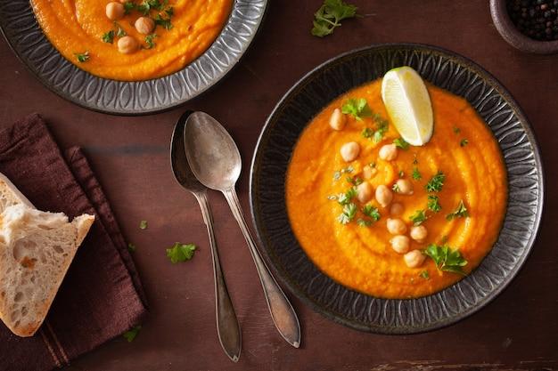 Sopa cremosa de grão de bico de cenoura no fundo rústico escuro