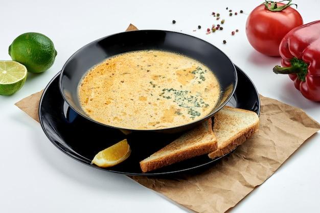 Sopa cremosa de salmão norueguesa clássica em um prato preto com torradas torradas em um prato branco