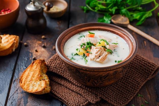 Sopa cremosa finlandesa quente com salmão e legumes em uma tigela de cerâmica velha na superfície de madeira velha. estilo rústico.