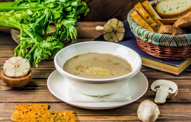 Sopa cremosa leitosa de cogumelos servida com biscoitos