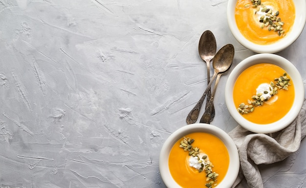 Sopa de abóbora caseira fresca com queijo ricota e sementes no fundo cinza de concreto. vista do topo. copie a área do espaço.