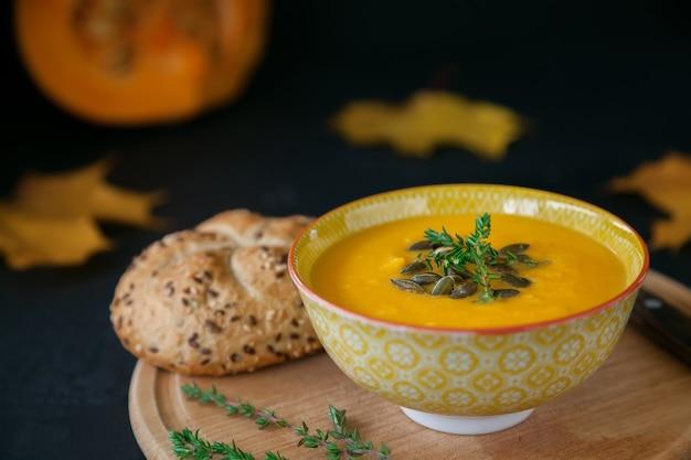 Sopa de abóbora caseira vegana de outono close-up com sementes, ervas e pão, em um fundo preto