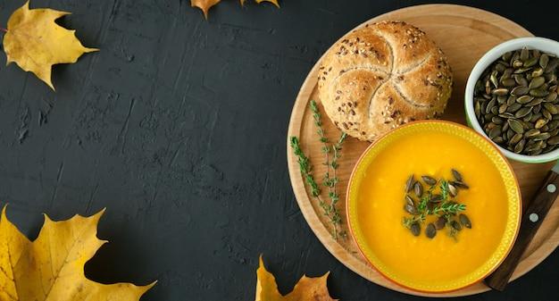 Sopa de abóbora caseira vegana de outono com sementes, ervas e pão, em um fundo preto, cópia-espaço, vista de cima